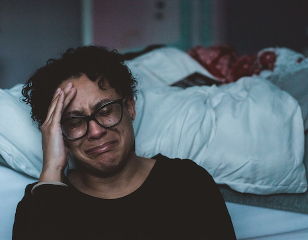 a woman crying next to her bed